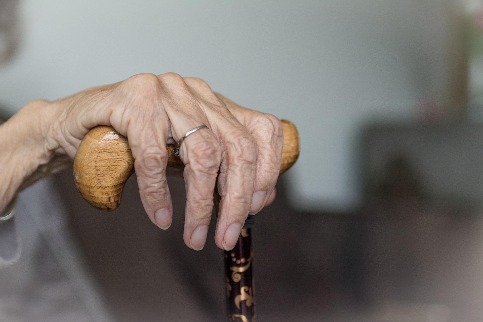 Old woman hand on cane in memory care facility